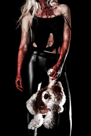 angry teddy: Bloody young woman holding a teddy bear over black background Stock Photo