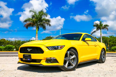 CANCUN, MEXICO - MAY 16, 2017: Yellow muscle car Ford Mustang in the city street.