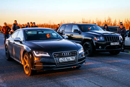 charged: YAMAL, RUSSIA - JUNE 16, 2017: Motor cars Audi S7 and Jeep Grand Cherokee SRT-8 take part in the night street drag racing.