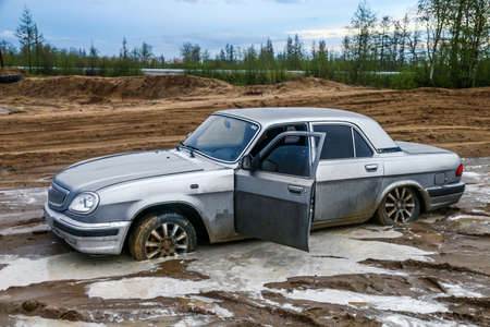 NOVYY URENGOY, RUSSIA - JUNE 19, 2017: Motor car GAZ 31105 Volga at the dirt road.