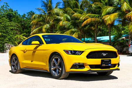 TULUM, MEXICO - MAY 17, 2017: Yellow muscle car Ford Mustang at the countryside.