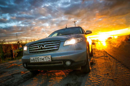 crossover: NOVYY URENGOY, RUSSIA - JULY 2. 2017: Grey motor car Infiniti FX35 at the background of the dawn during the midnight sun.