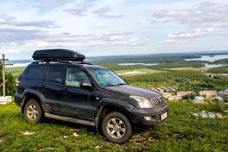 REGIÓN DE CHELYABINSK, RUSIA - 8 DE JULIO DE 2017: coche todoterreno negro Toyota Land Cruiser Prado 120 en el campo. Editorial
