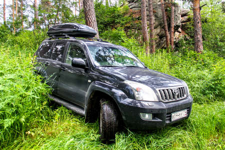 toyota: CHELYABINSK REGION, RUSSIA - JULY 8, 2017: Black off-road car Toyota Land Cruiser Prado 120 at the countryside. Editorial