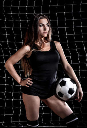 Beautiful young woman with a football over the black background with a net