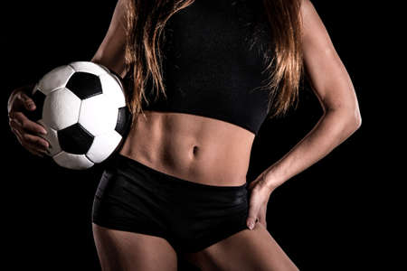 Torso of a sexy woman with a football over black background
