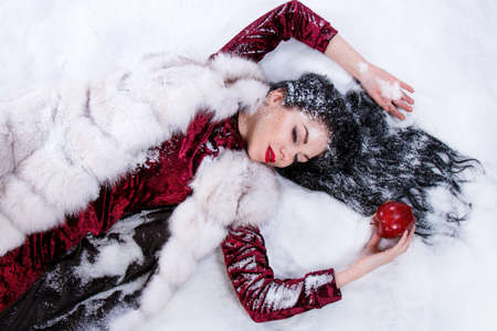 Pretty young woman laying on a snow near the red bitten apple Stock Photo