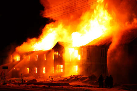 Burning old wooden house at night Stock Photo