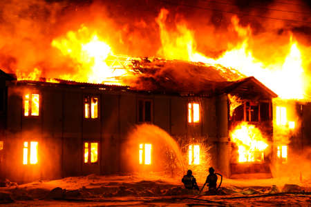 Burning old wooden house at night