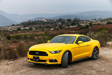 sportcar: HIERVE EL AGUA, MEXICO - MAY 26, 2017: Yellow muscle car Ford Mustang at the countryside.