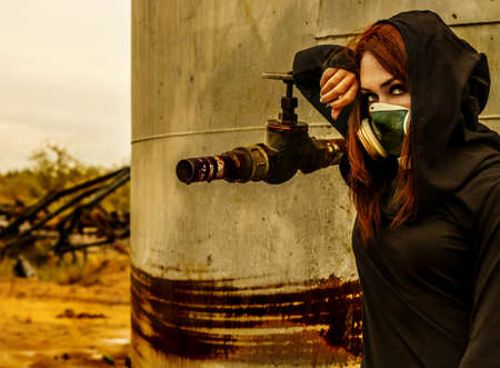 Woman in the gas mask at the background of the rusty structure
