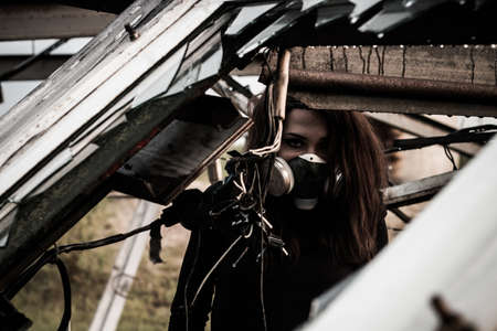 Woman in the gas mask inside the rusty structure