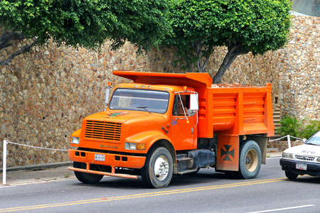 Acapulco, Mexico - May 31, 2017: Orange dump truck Dina S-500 in the city street.