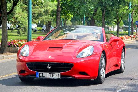 Budapest, Hungary - July 26, 2014: Red sports car Ferrari California in the city street. Sajtókép