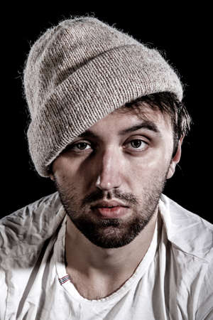 Unshaven man in a knitted hat over black background