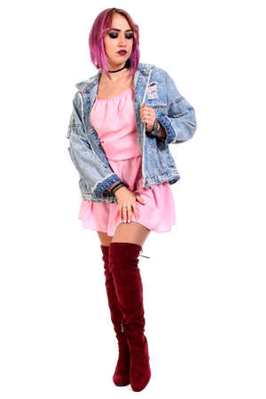 Beautiful young woman with a purple hair in a pink dress and jeans jacket isolated over white background