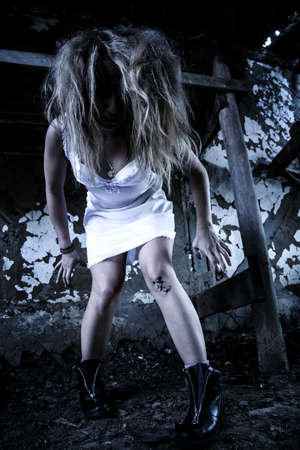 Mad woman in a white nightie in the abandoned building