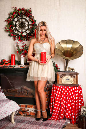 Pretty young woman in a short dress in the Christmas decorated room Stock Photo