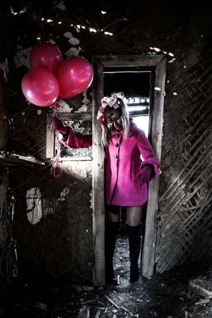 Zombie girl in a pretty pink coat walking through the broken door Stock Photo
