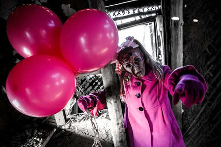 Zombie girl with a bunch of pink balloons in a pretty pink coat Stock Photo