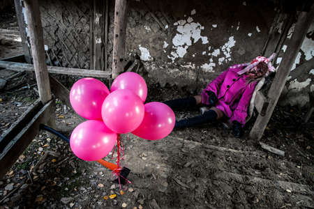 Balloons at the background of a dead girl in a pretty pink coat Stock Photo
