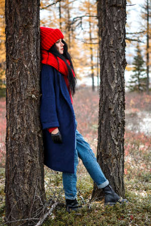 Pretty young woman in a red hat and scarf walking in the forest Stok Fotoğraf