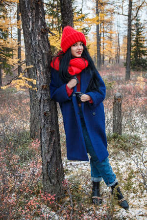 Pretty young woman in a red hat and scarf walking in the forest Stock Photo