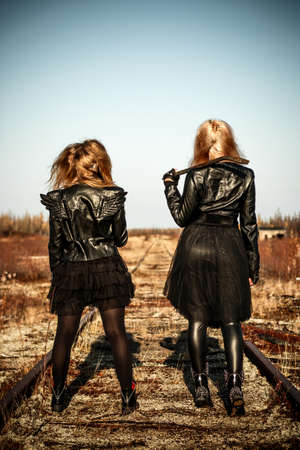 Two women in a black leather clothes staying on the abandoned railway