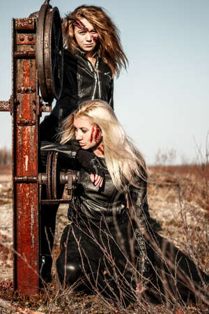Two scratched women in a black leather clothes near the railway switcher Stock Photo