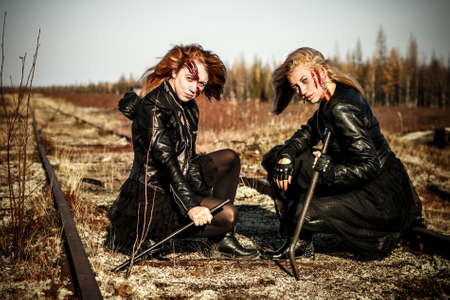 Two scratched women in a black leather clothes sitting on the abandoned railway Stock Photo