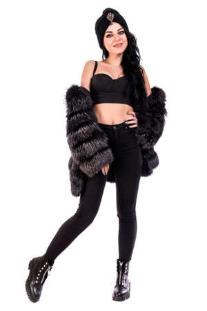 Pretty young woman in a black fur coat and turban isolated over white background Stock Photo