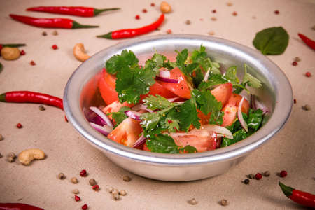 Sliced fresh tomatoes and onions at the background of the chili pepper, cashew nuts and green leaves