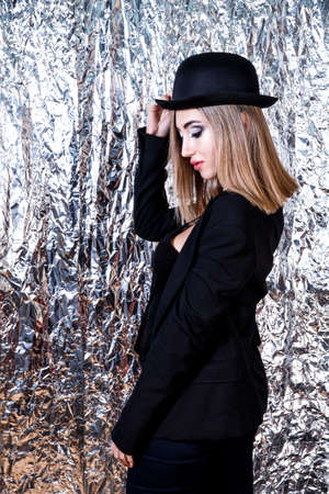 Beautiful young woman in a black hat and a black jacket at the aluminium foil background