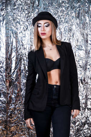 Beautiful young woman in a vintage black suit at the aluminium foil background