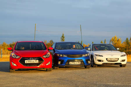 Novyy Urengoy, Russia - August 30, 2015: Red, blue and white cars in the city street.