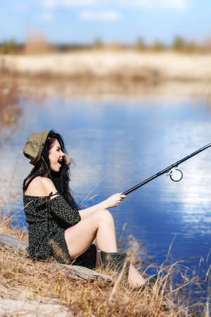Woman fishes on the lake in a sunny day