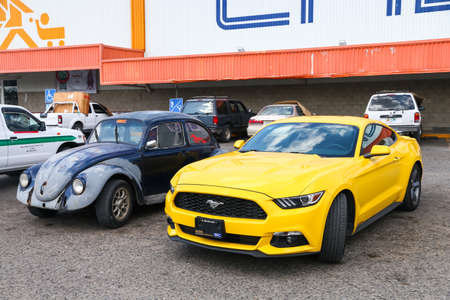 Palenque, Mexico - May 22, 2017: Yellow muscle car Ford Mustang and old car Volkswagen Beetle in the city street.