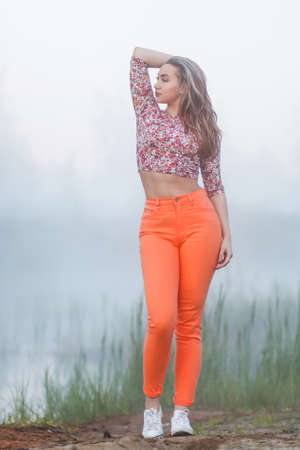 Young woman in a bright orange jeans near the foggy lake
