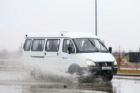Novyy Urengoy, Russia - May 31, 2016: Passenger van GAZ 3221 Gazelle in the city street during a heavy flood. 에디토리얼