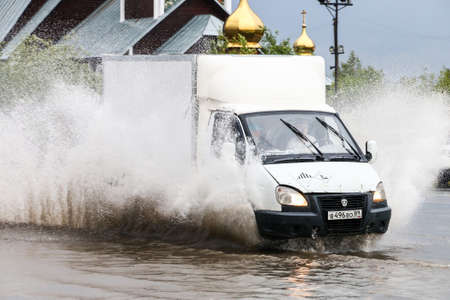 Novyy Urengoy, Russia - August 14, 2018: Motor car GAZ 3302 Gazelle in the city street during a heavy flood.