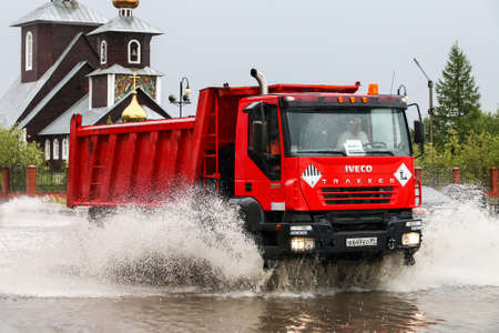 Novyy Urengoy, Russia - August 14, 2018: Red dump truck Iveco AMT Trakker in the city street during a heavy flood.