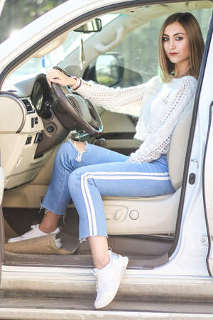 Pretty young girl in a casual clothes sitting in the modern luxury off-road car 免版税图像
