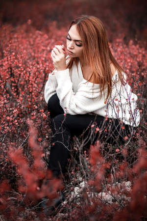 Woman in a white warm jacket sitting in the red bushes