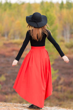 Young woman in a red skirt at the background of the autumn scenic Stock Photo