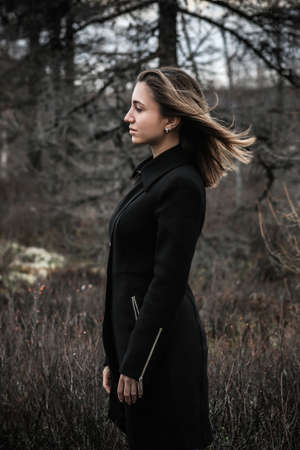 Young woman in a black coat in a dark forest
