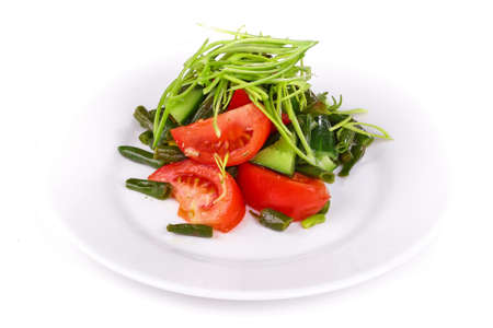 Salad of tomatoes and cucumbers on a white plate isolated over white