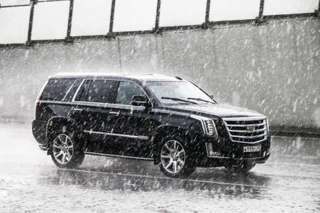 Moscow, Russia - May 2, 2018: Luxury SUV Cadillac Escalade in the city street during a heavy rain.