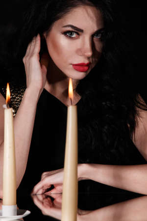 Young woman behind the candle over black background