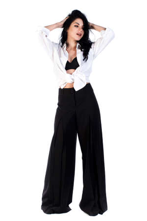 Pretty young woman in a wide shirt and trousers isolated over white background