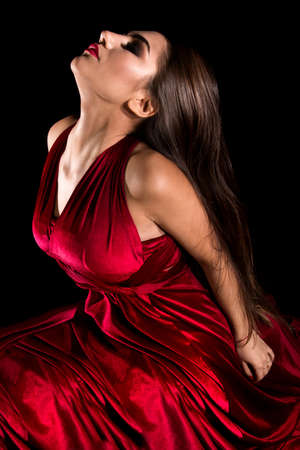 Young woman sitting in a red dress over black background